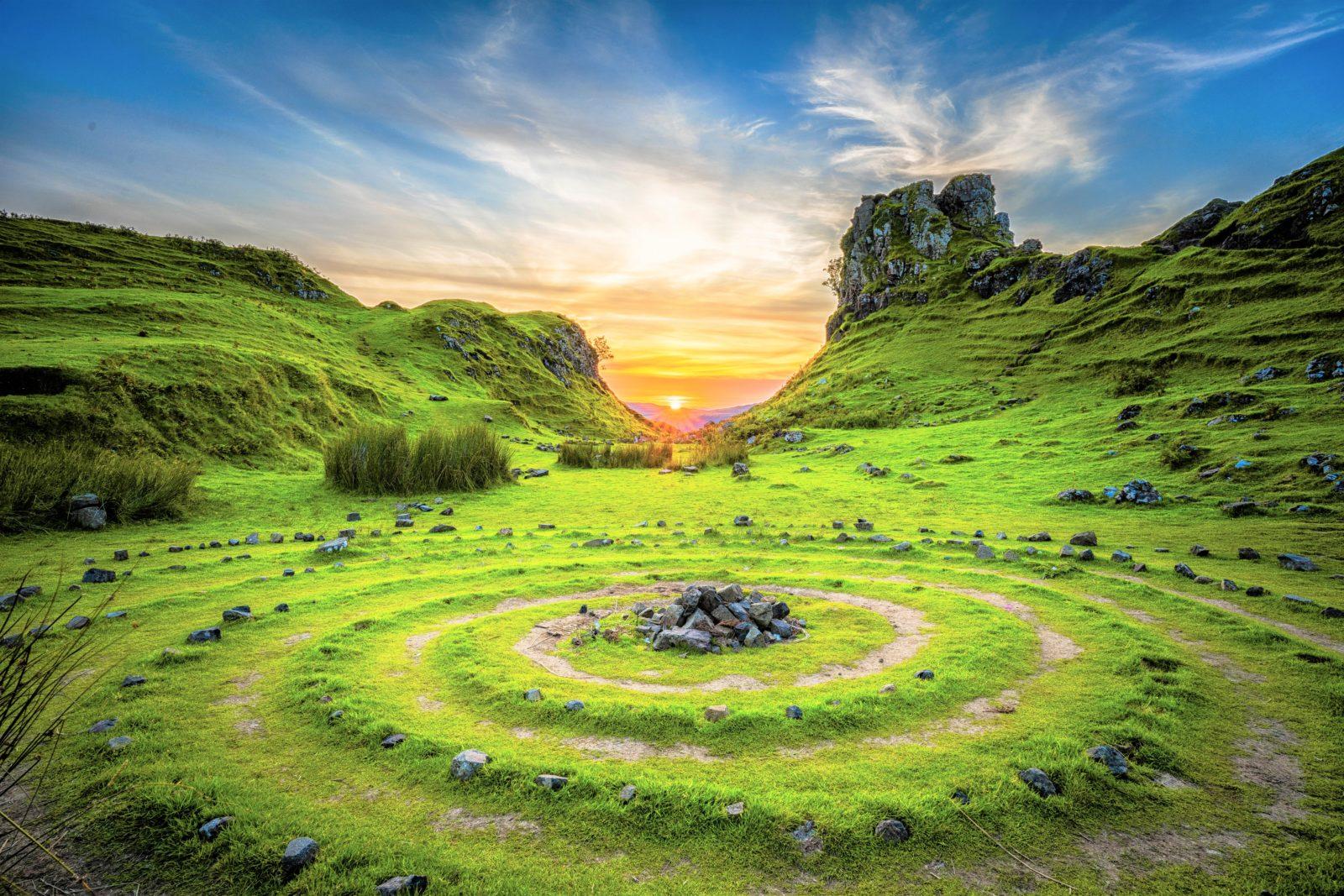 Prato Con Delle Rocce Circondate Da Cerchi E Sullo Sfondo Il Sole Che Sorge